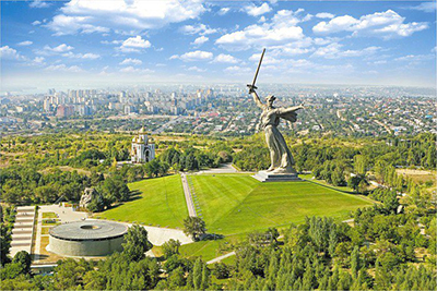 This is a photo showing the gigantic statue standing on a hill,  surrounded by trees and the memorial chamber with its eternal flame and guards. There is also a Russian Orthodox church  at the memorial complex.