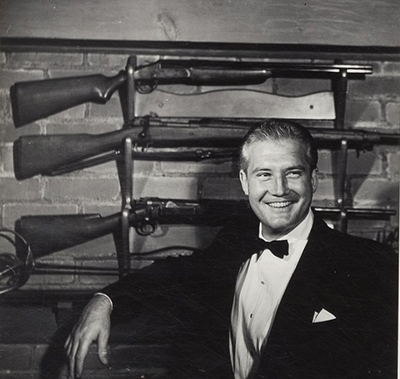 photo of George standing in front of three rifles  displayed on the wall of his den.