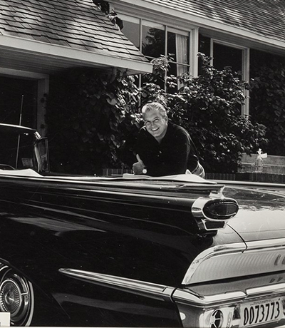 photo of George standing by his car. He's smiling.